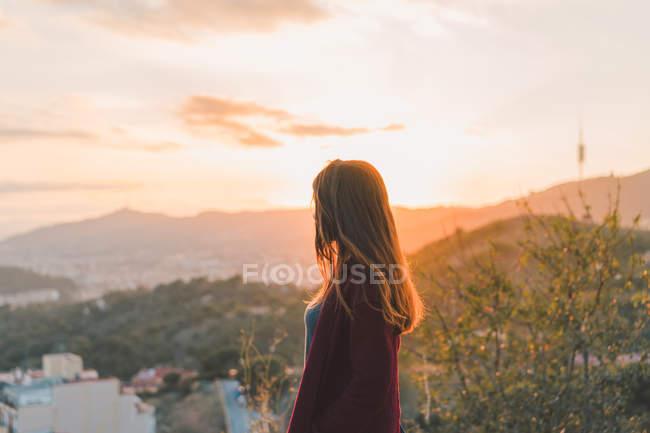 Vista lateral de la mujer en la colina en la luz del atardecer - foto de stock