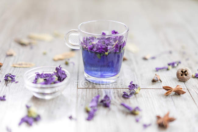 Glass of brewed Butterfly Pea tea with tender petals on wooden table. — Stock Photo