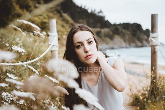 Zarte brünette Frau bei Blumen an der Küste — Stockfoto