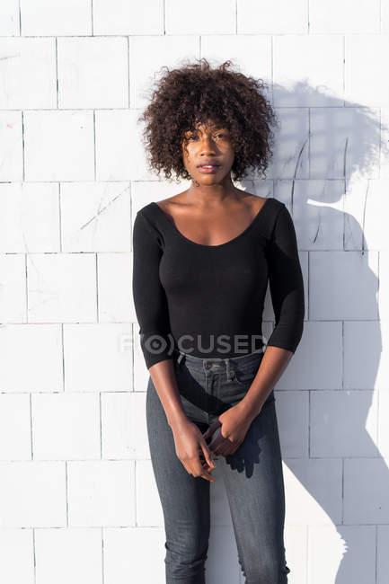 Mulher étnica elegante posando na parede branca — Fotografia de Stock