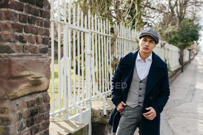 Stylish man in vintage clothes posing near gate — Stock Photo