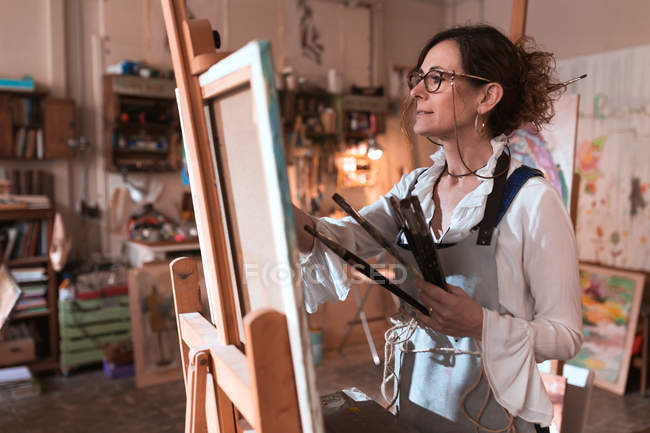 Adult woman drawing picture in workshop. — Stock Photo