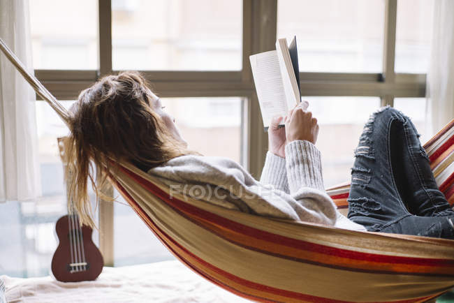 Side view of woman in hammock relaxing with book — Stock Photo