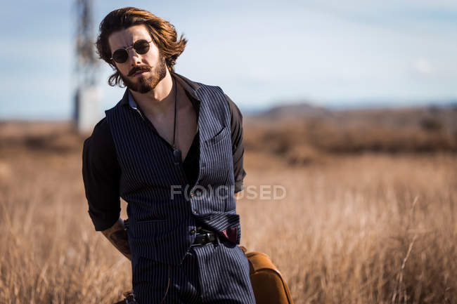 Man in sunglasses posing on dry field — looking at camera