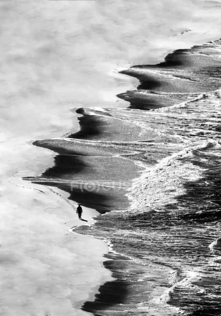 Vista aérea do turista irreconhecível caminhando na costa arenosa no mar ondulado . — Fotografia de Stock