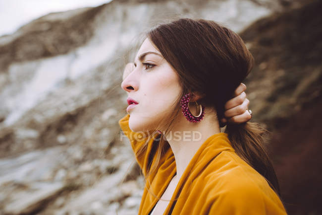 Wonderful brunette girl in yellow jacket holding hair in pony tail — Stock Photo