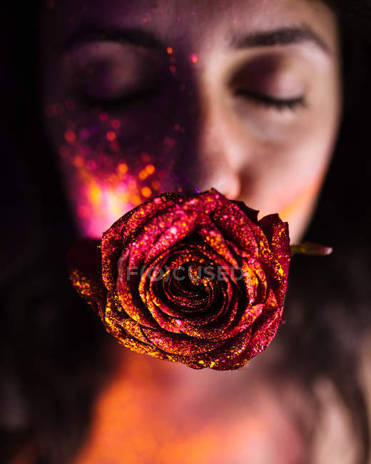 Young pretty woman with glittering and fluorescent red rose in mouth. — Stock Photo