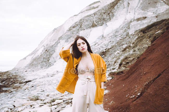 Brunette girl in bra and yellow jacket posing over rocky cliff — Stock Photo