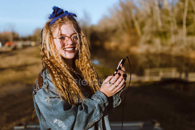 Smiling curly blonde girl in headphones looking at camera over nature — Stock Photo
