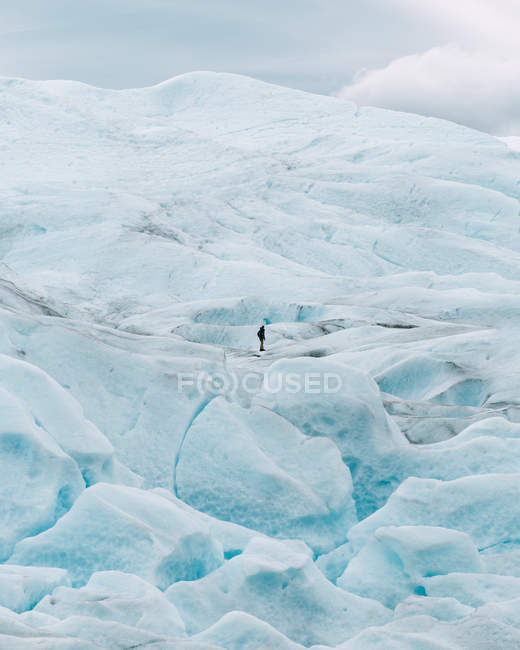 Distant view of tourist standing on snowy hill — Stock Photo