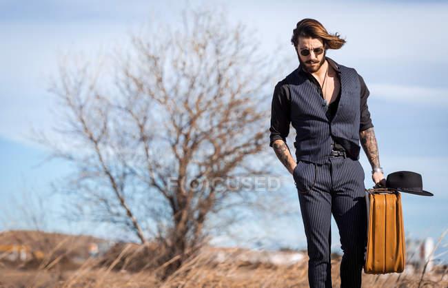 Uomo alla moda con valigia e cappello che cammina alla campagna campo —  Foto stock efd7b91983c7
