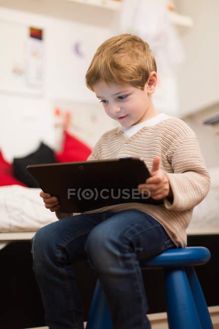 Ragazzo biondo seduto a casa e giocare con tablet — Foto stock