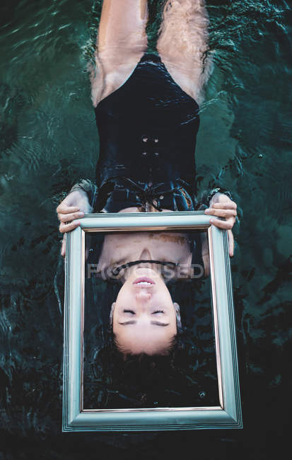 Brunette woman swimming with frame — Stock Photo