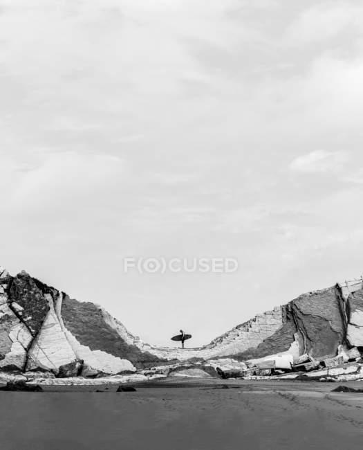 Серфер, стоячи з ради на тлі двох пагорбів на узбережжі. — стокове фото