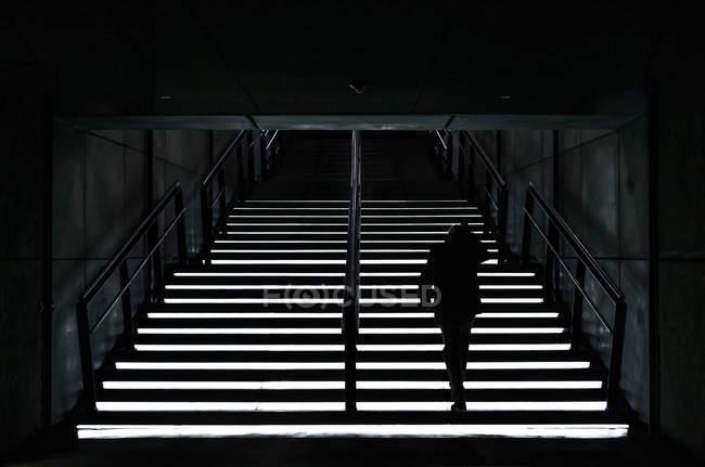 Rückansicht einer Frau, die auf beleuchteten Treppen nach oben geht. — Stockfoto