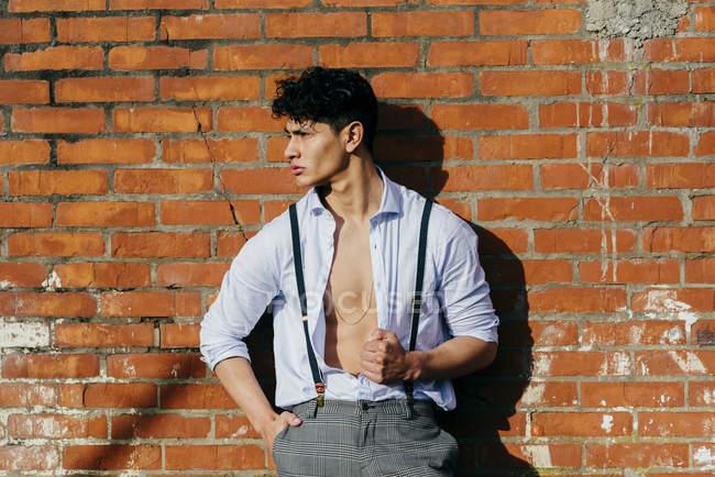 Uomo in camicia a bottone appoggiato al muro e guardando da parte — Foto stock