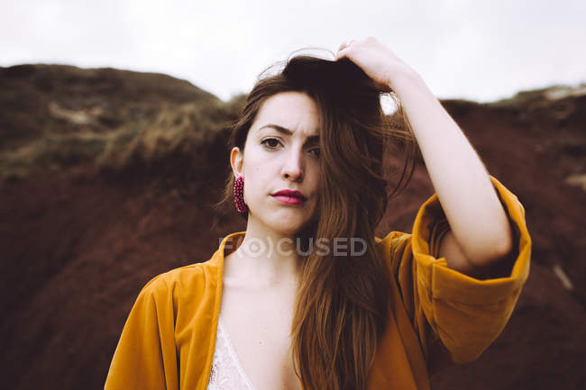 Brunette woman in yellow jacket adjusting hair and looking at camera — Stock Photo