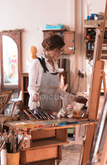 Woman standing and drawing paint in workshop. — Stock Photo