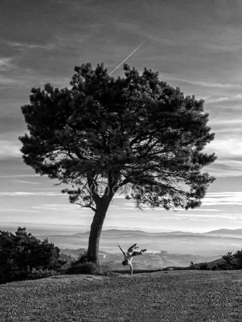 L'homme debout sur place et en effectuant des truc à l'arbre dans la nature. — Photo de stock