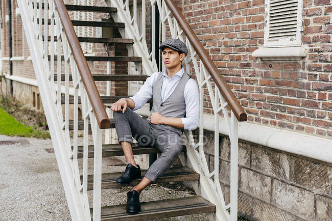 Cheerful man in vintage clothes and cap sitting on stairs — Stock Photo
