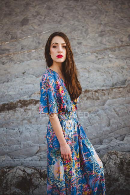Tender brunette girl in blue dress over rocky terrain — Stock Photo