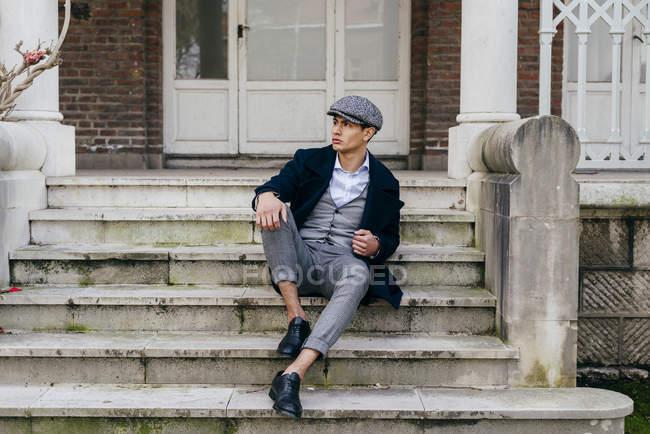 Человек в винтажной одежде сидит на крыльце и смотрит в сторону — стоковое фото