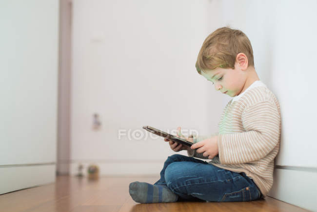 Side view of blonde boy playing with tablet while sitting on floor — Stock Photo