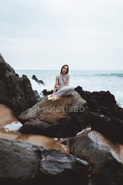 Femme brune en robe longue assis sur rocher mouillé au littoral océanique — Photo de stock