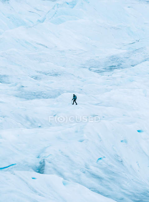 Side view of tourist walking on snowy hill — Stock Photo