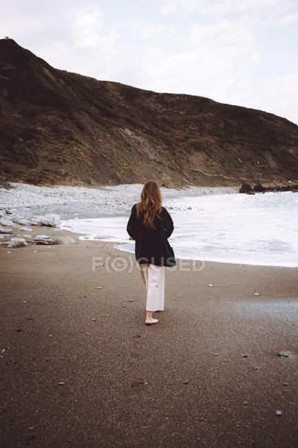 Rear view of woman walking on ocean shoreline — Stock Photo