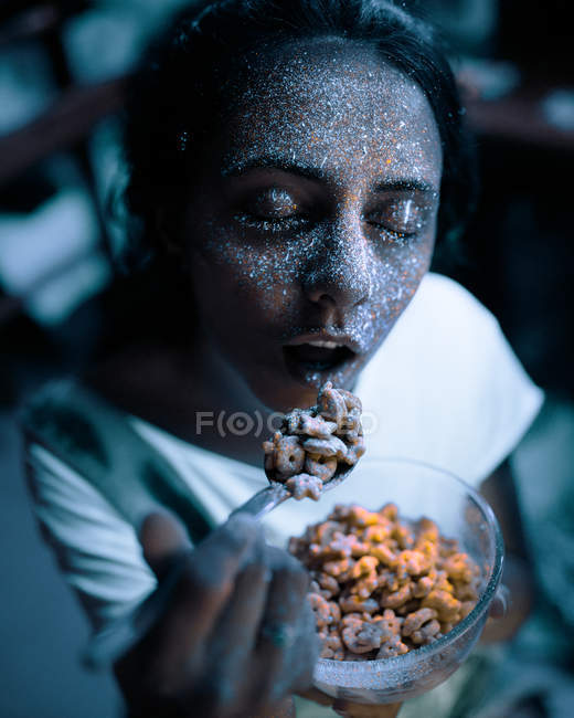 Pretty woman with gray glittering fluorescent paint on face eating cereal with eyes closed. — Stock Photo