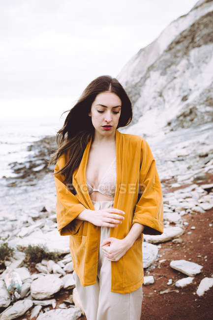 Brunette woman in bra and yellow jacket waking at coastline — Stock Photo