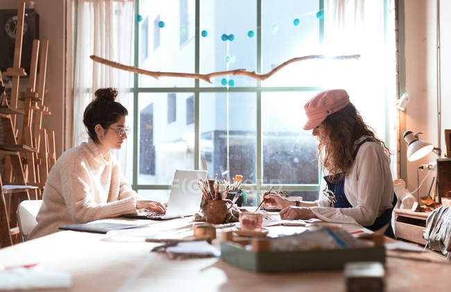 Two women working at one table in workshop — Stock Photo