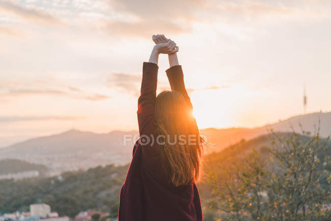 Visão traseira da mulher esticando as mãos na colina na luz do pôr do sol — Fotografia de Stock