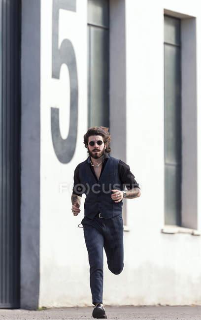 Stylish man in sunglasses running on street. — Stock Photo