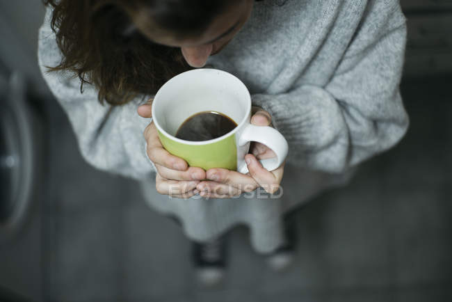 Crop woman standing and drinking coffee — Stock Photo