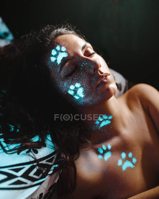 Young woman with blue fluorescent animal paw prints on face with eyes closed. — Stock Photo