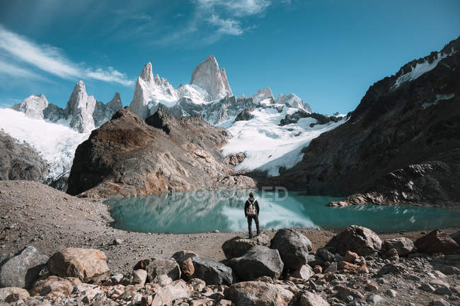 Back view of backpacker standing at small lake in mountains covered with snow. — Stock Photo