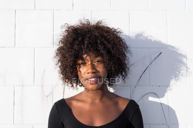 Усміхається жінка постановки на білі стіни і дивлячись на камеру — стокове фото