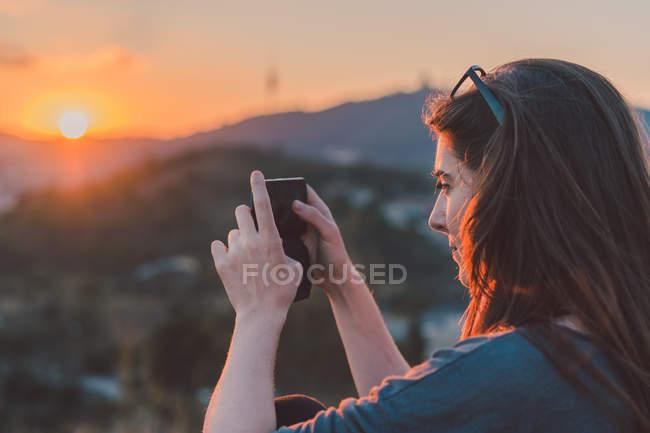 Frau nehmen Foto mit Smartphone auf Hügel im Sonnenuntergang leuchten — Stockfoto