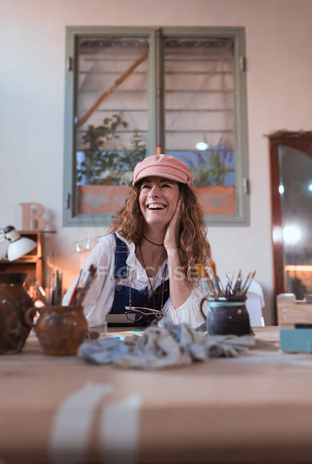 Cheerful painter with brush at table in workshop — Stock Photo