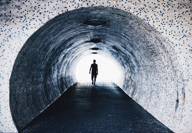 Silhouette zu Fuß in gefliestem Tunnel. — Stockfoto