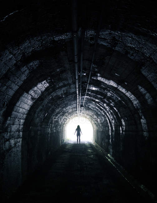 Creepy silhouette standing in tunnel with light in end. — Stock Photo