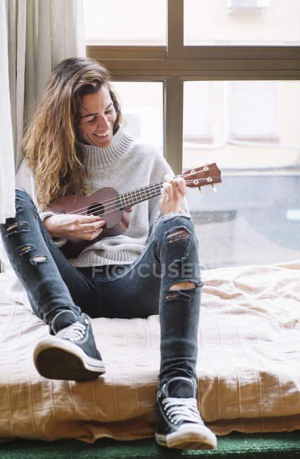 Cheerful woman playing ukulele at window sill — Stock Photo