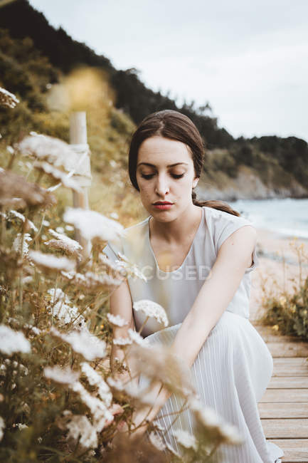 Tender brunette woman with flower on coast — Stock Photo