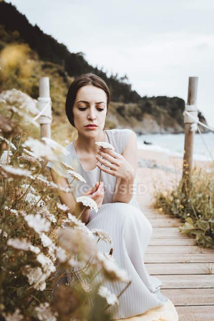 Zarte brünette Frau mit Blume in den Händen an der Küste — Stockfoto