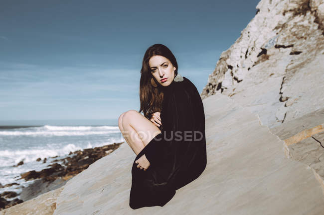Model in black coat sitting on coastline and looking at camera — Stock Photo
