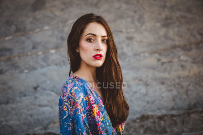 Brunette woman with red lips walking on rocky terrain and looking at camera — Stock Photo