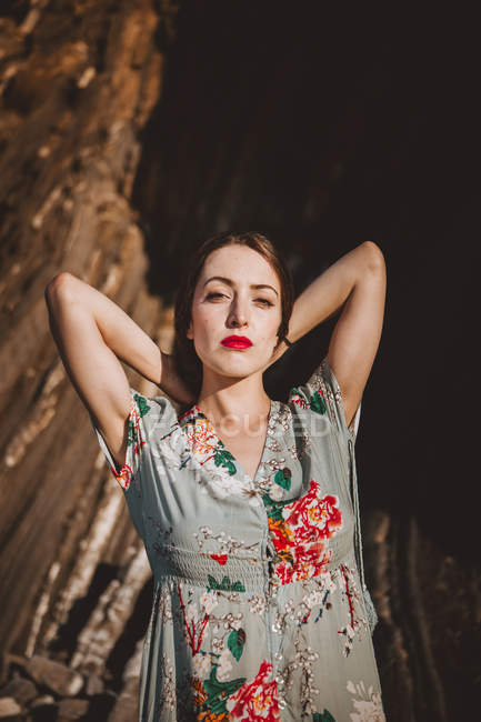 Young brunette with red lips wearing elegant ornamental dress posing in sunlight. — Stock Photo