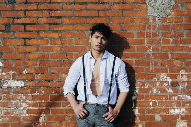 Mann im aufknöpften Hemd lehnt an Ziegelwand und blickt in Kamera — Stockfoto